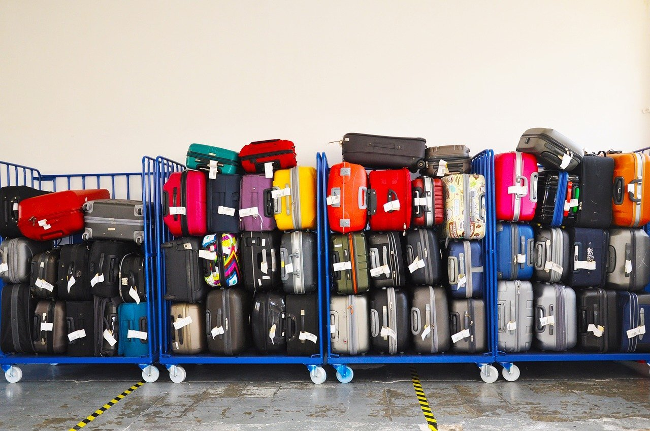 the best travel luggage: a pile of suitcases on racks at an airport